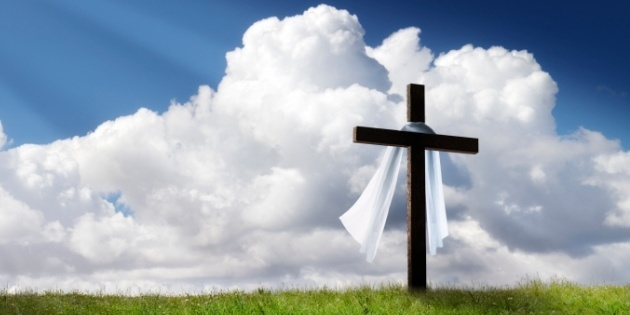 Cross with white cloth against blue sky